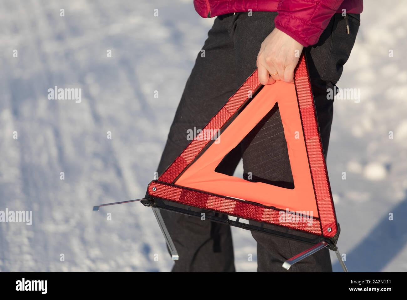 Autoilija pulassa talvella ja asettamassa varoituskolmiota sekä soittamassa apua. Stock Photo