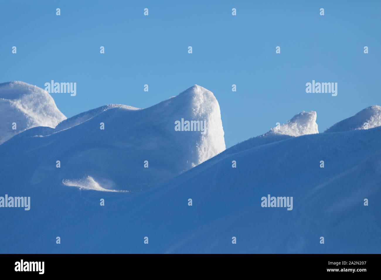 Dyynimäiset lumihangen muodot taivasta vasten Stock Photo