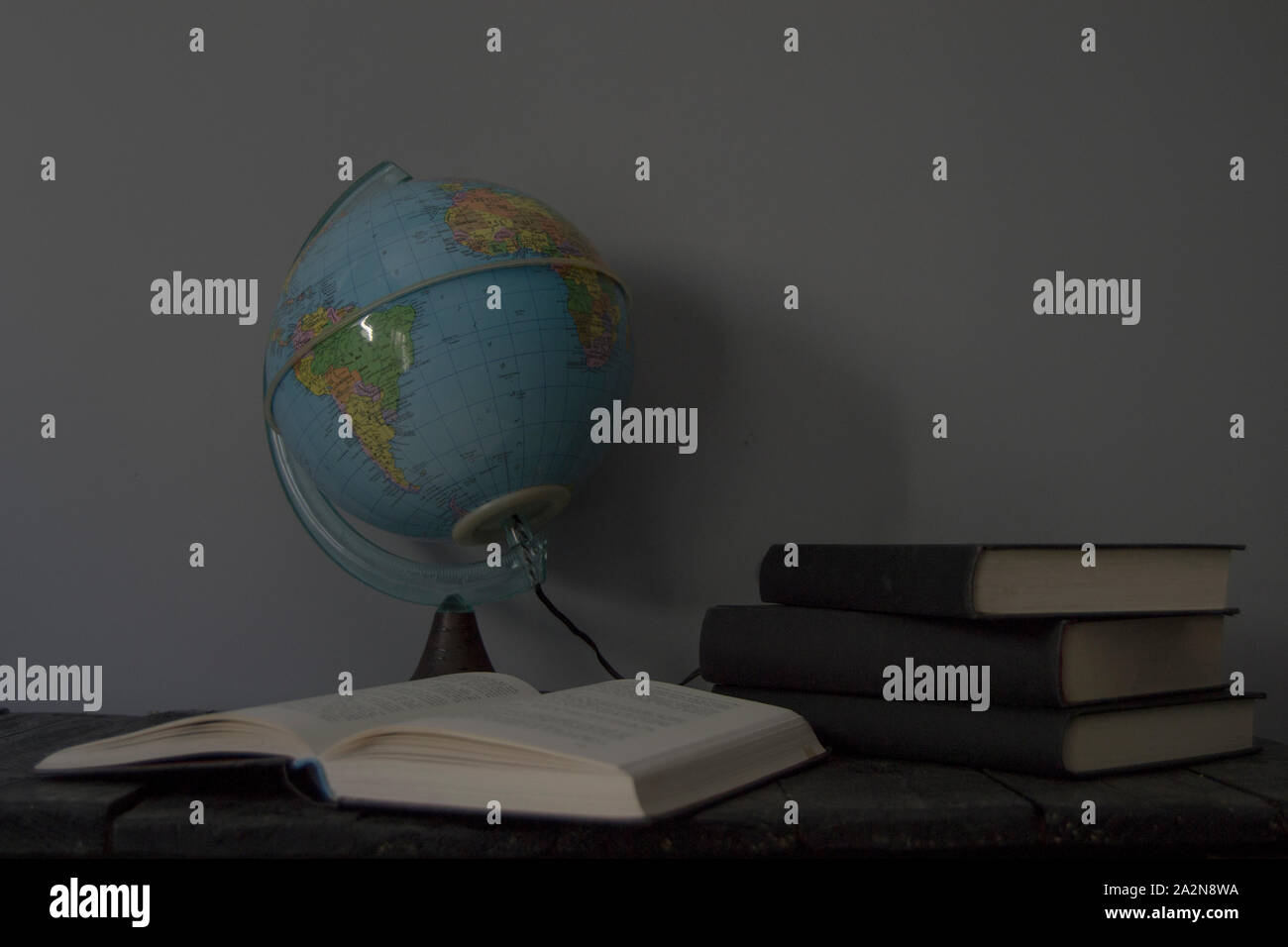 Earth ball with books on gray background Stock Photo