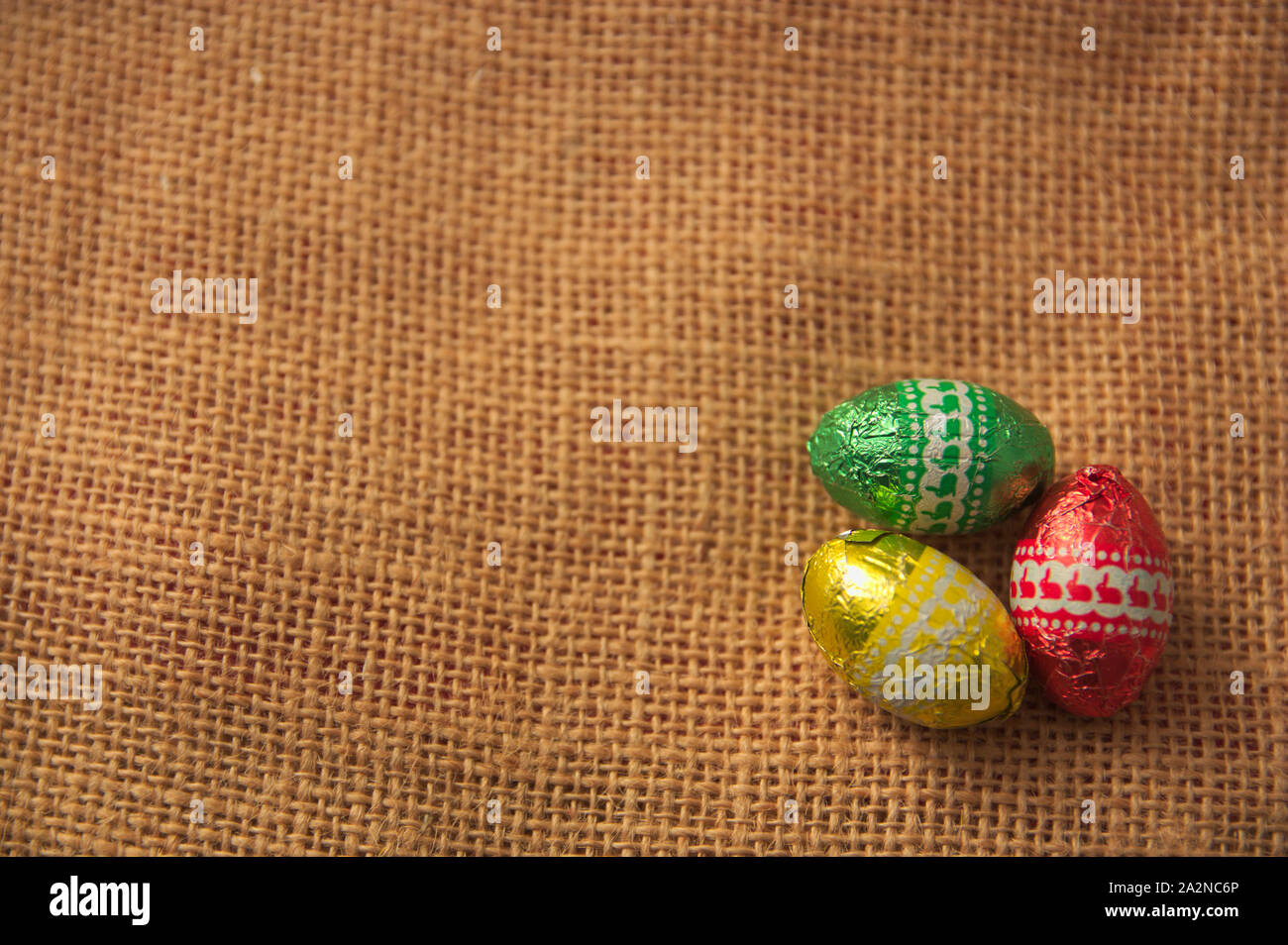 A decorative background for Easter with brightly colored eggs on a brown sackcloth and space to add texts or graphics. Copy Space Stock Photo