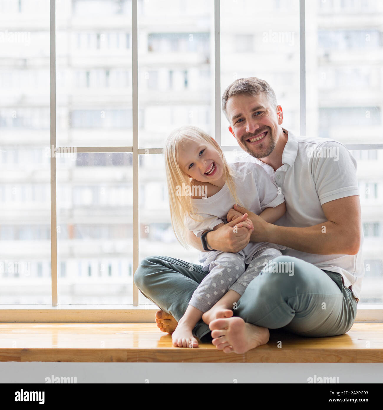 Young Man Holding Her 3 5 Years Old Daughter While Sitting On