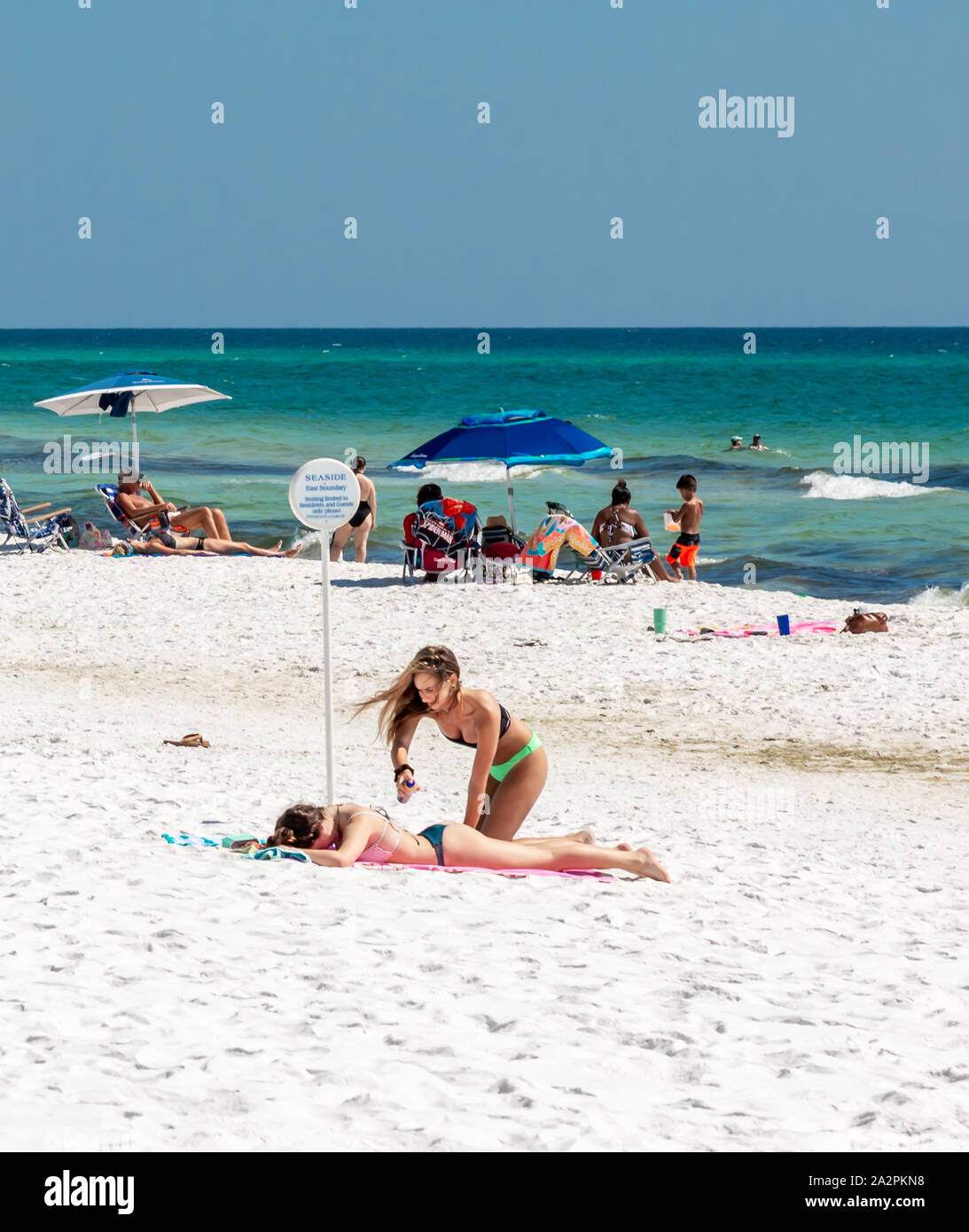 two teenage girls with people in the background on the beach at Seaside, FL Stock Photo