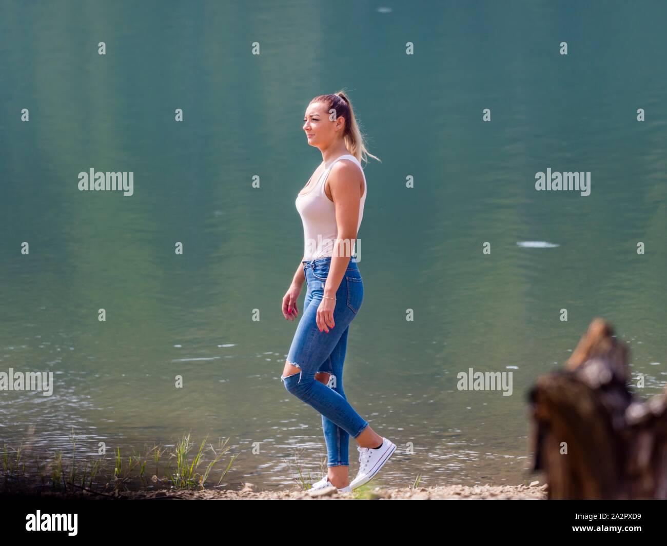 Young woman wearing Blue denim pants denims is walking along lake coastline Stock Photo