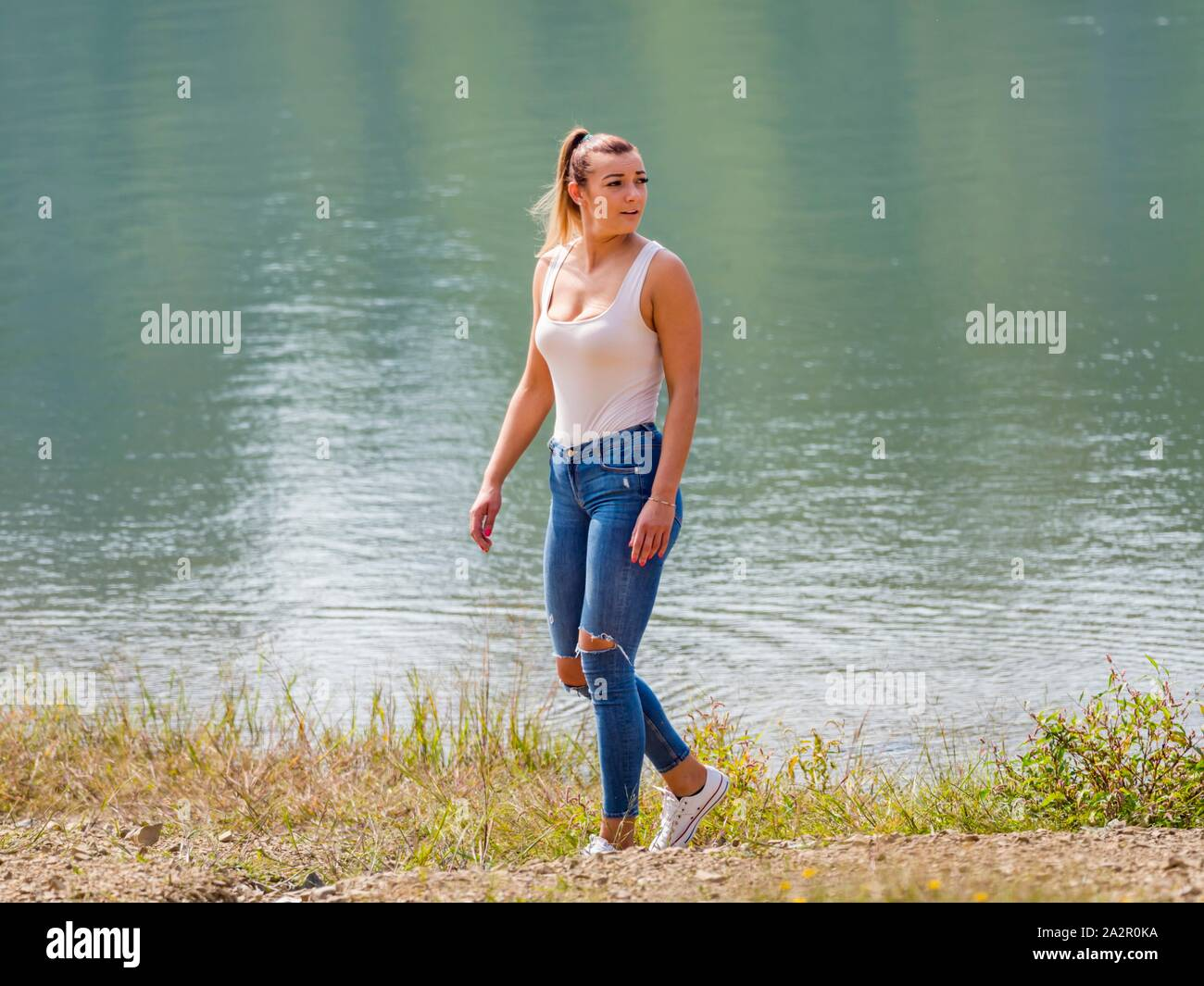 Young woman wearing Blue denim pants denims is walking along lake coastline looking back suspiciously cautiously Stock Photo