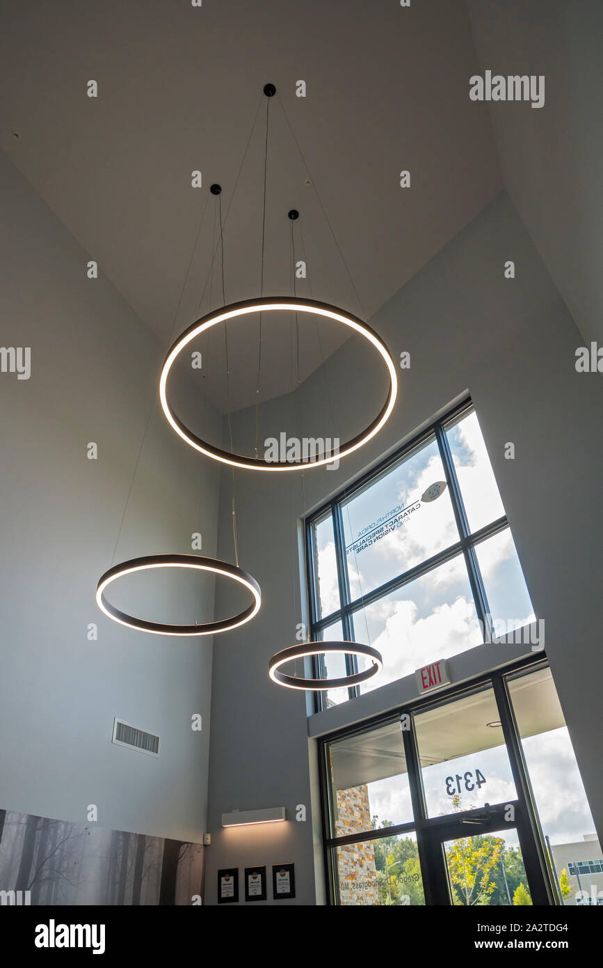 Large circular lights hanging from the ceiling inside a doctor's office entrance. Stock Photo