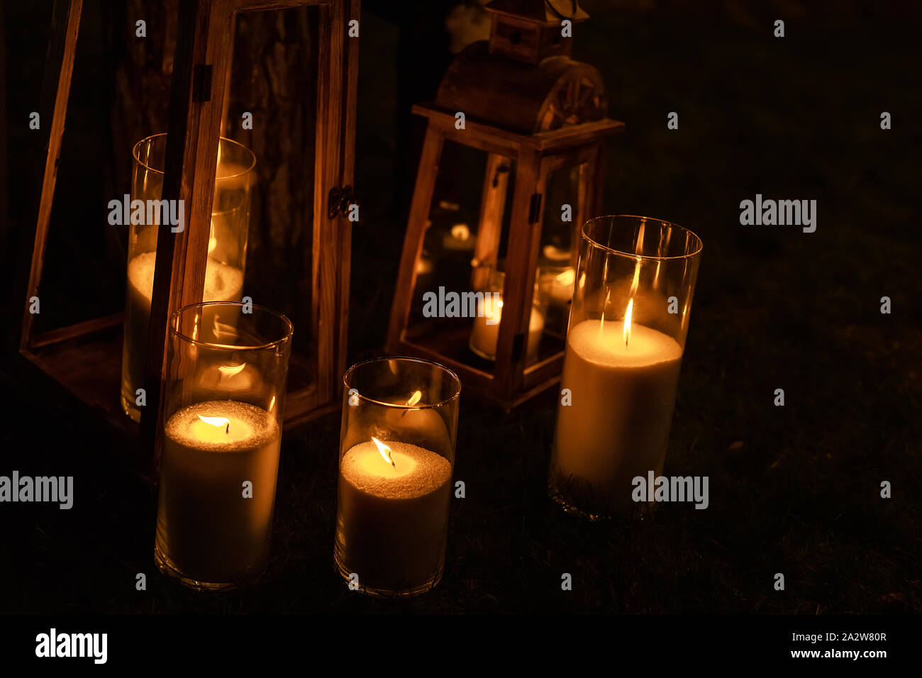 Many burning candles in glass and wooden lanterns on dark ground outdoor at night. Romantic party area. Diwali fire holiday Stock Photo