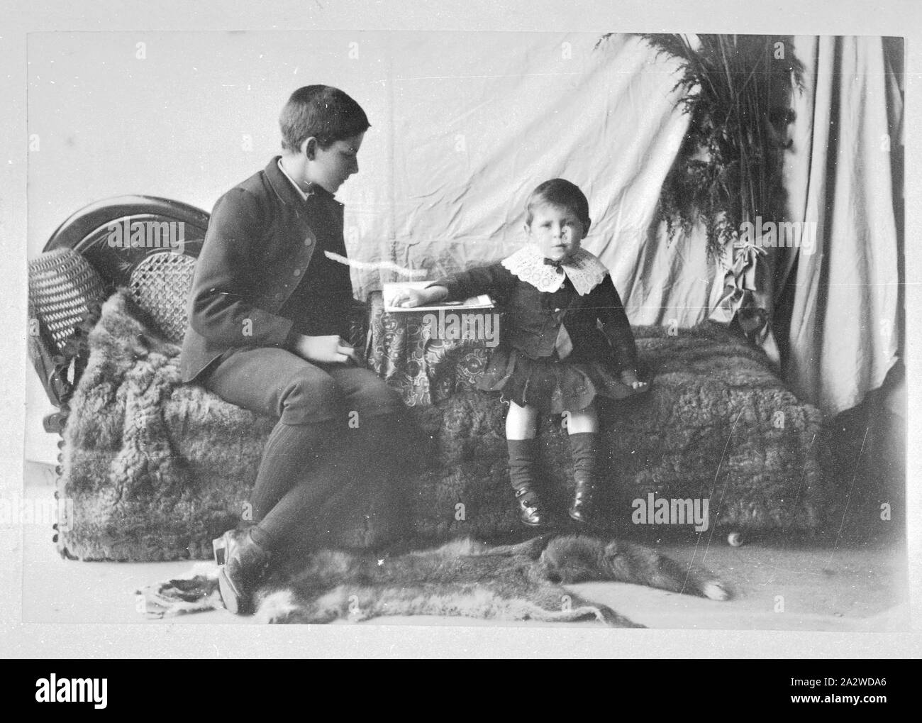 Photograph - by A.J. Campbell, Victoria, circa 1890, A studio photograph of two boys seated on a sofa. The younger boy rests his arm on what may be a games board while the older boy is looking at the board. The sofa is covered by a possum (?) skin rug Stock Photo