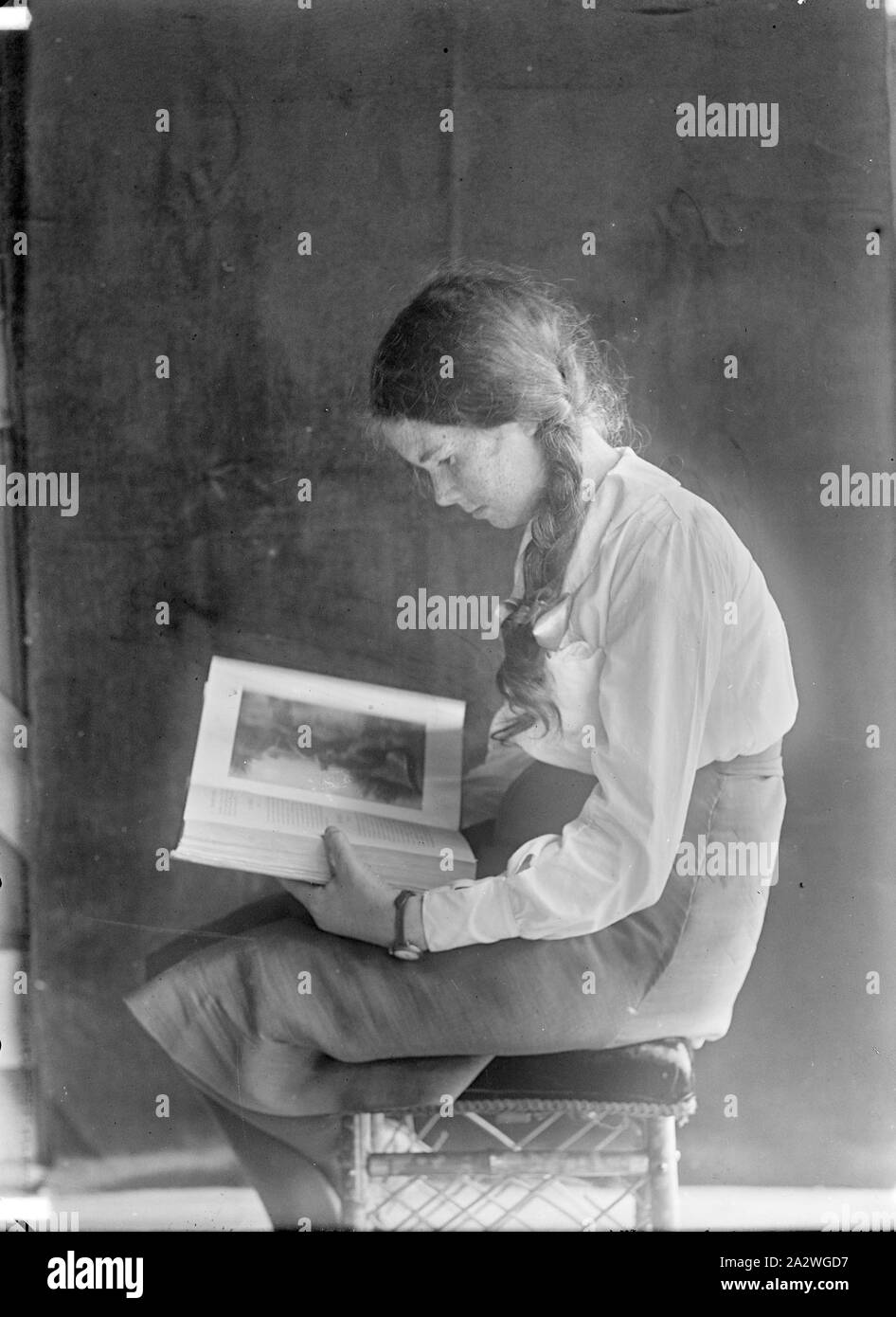 Glass Negative - Jean Wentworth Harvie Reading a Book, Melbourne, circa 1917, Glass plate negative portrait of Jean Wentworth Harvie, probably between the ages of 12 and 14 years. It is thought that this photograph was taken by her father, studio photographer, Robert Harvie. There is a similar photograph of her sister, Ellison Harvie. Robert William Harvie was a professional photographer who, with his business partner Albert Stock Photo