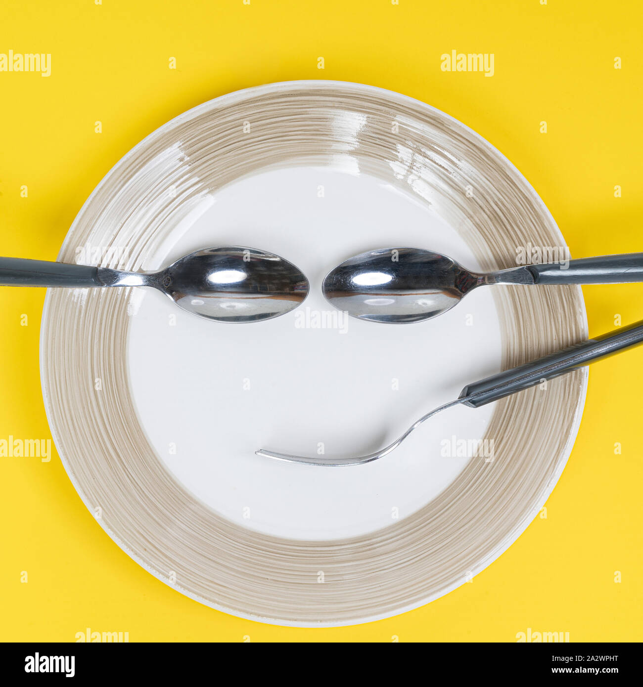 the crockery placed on the plate to form a smiling face Stock Photo