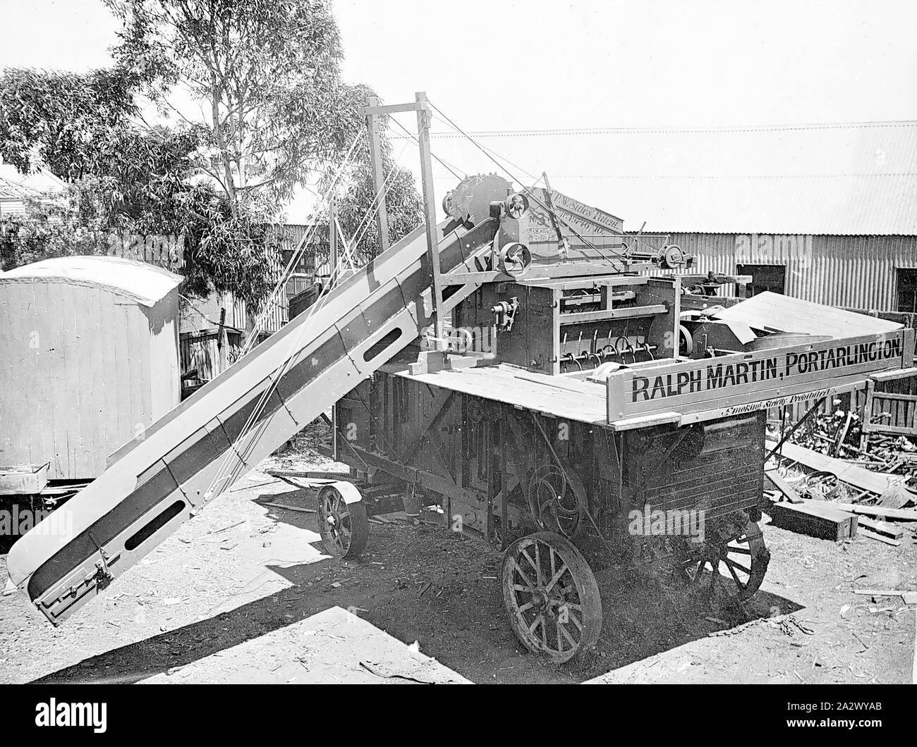 Negative - Threshing Machine, Ralph Martin, Portarlington, Victoria, circa 1915, Travelling threshing machine of contractor Ralph Martin, Portarlington, Victoria. The threshing machine is fitted with a patent sheaf elevator and feeder labelled P.W. Sides' Patent, No.19746/10. No.3, Sawmill, ???, Geelong. The is a living van with a curved roof visible in the background Stock Photo