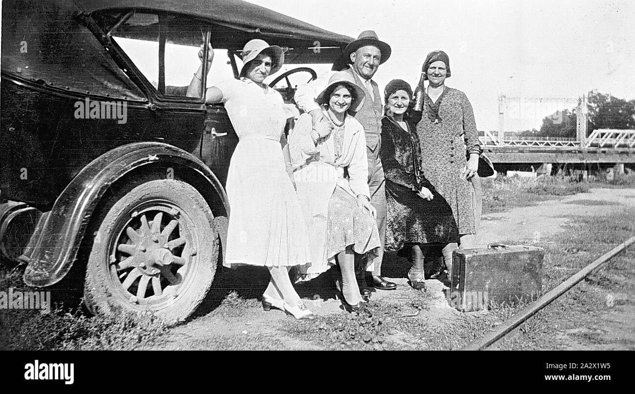 Negative - Swan Hill, Victoria, circa 1930, A man and four women beside a car. A bridge over the Murray River is in the background. There is a suitcase on the ground in front of the group while a railway line is visible at the bottom right hand corner Stock Photo