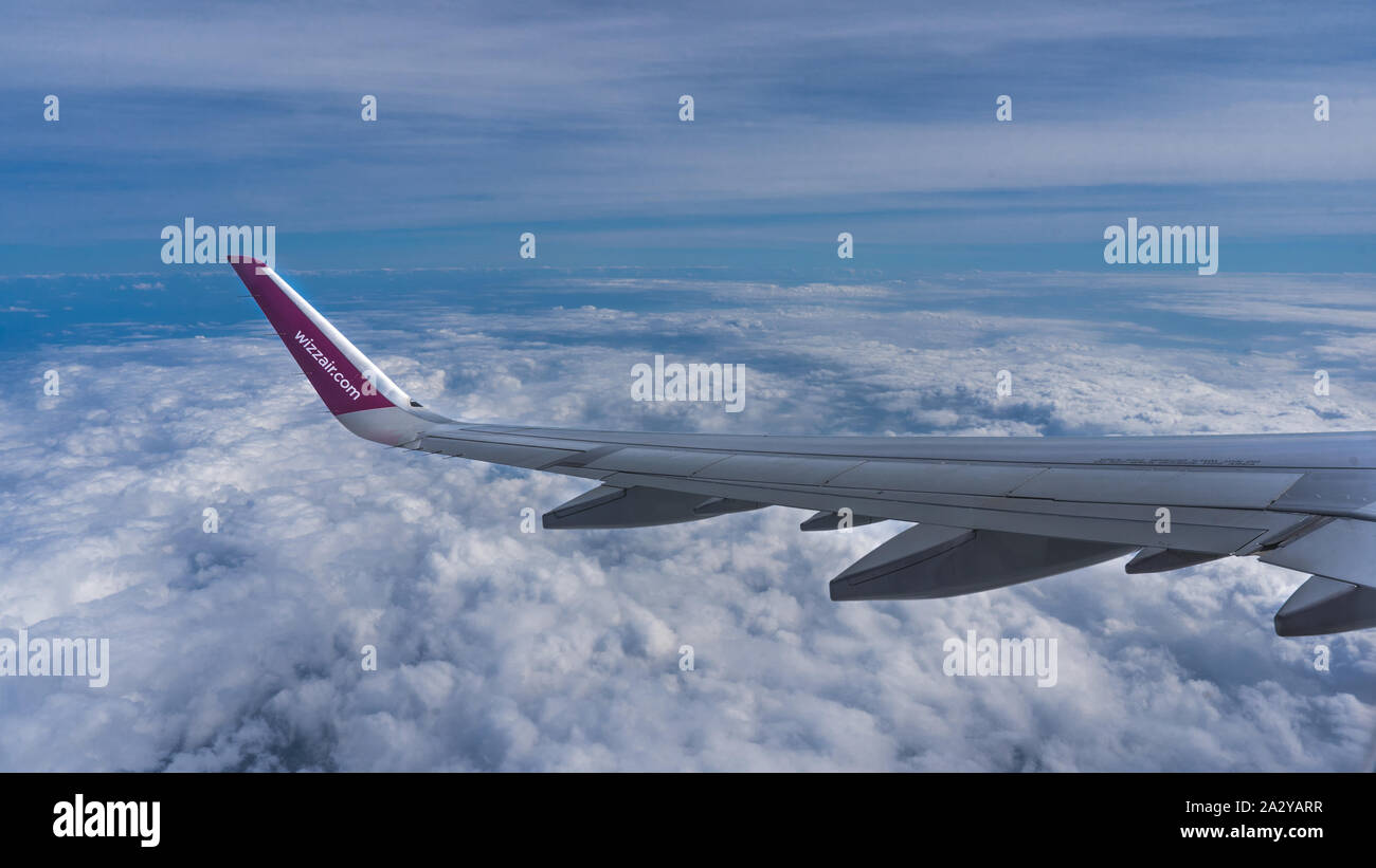 Clouds and a wing of Wizzair airbus from the airplane window. Above the clouds, view from the window Stock Photo