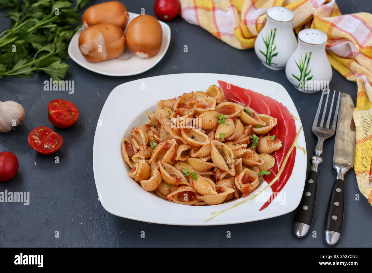 Conchiglie Italian pasta shells with cherry tomatoes and tomato sauce on dark background, horizontal orientation, closeup Stock Photo