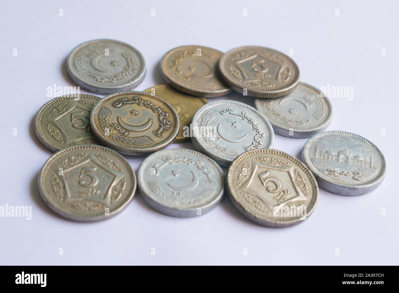 close up of pile of pakistani five rupee coins isolated on white background Stock Photo