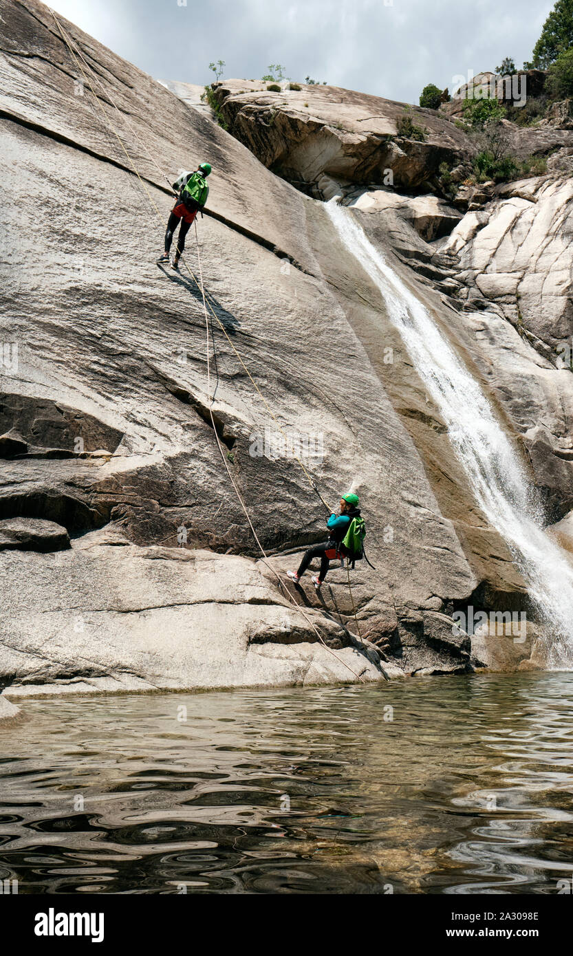 Tourists abseiling / rappelling / canyoning the Cascades de Purcaraccia, Quenza in the Corsica mountains near Bavella - Corsica adventure holiday Stock Photo