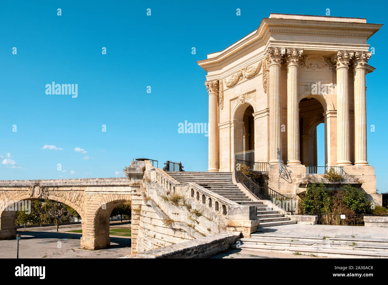 a view of the Promenade du Peyrou esplanade in Montpellier, France, highlighting its iconic neoclassical water tower on the left, and the Saint Clemen Stock Photo