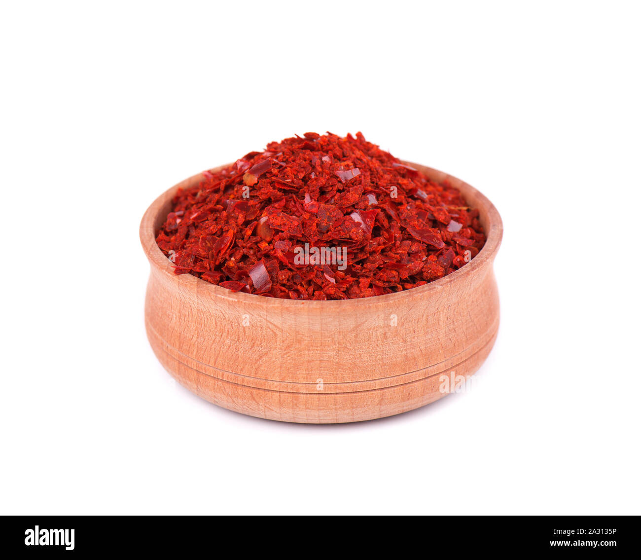 Pile crushed red cayenne pepper, dried chili flakes isolated on white background. Crushed red hot pepper in wooden bowl isolated on white. Stock Photo