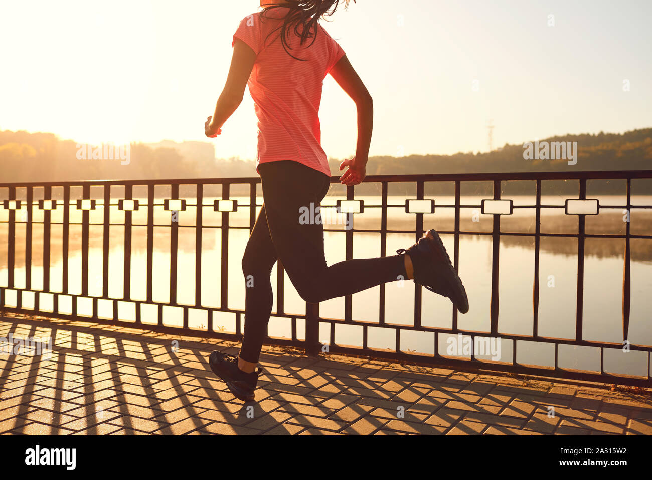 Runners legs run along the road by the lake in the park Stock Photo