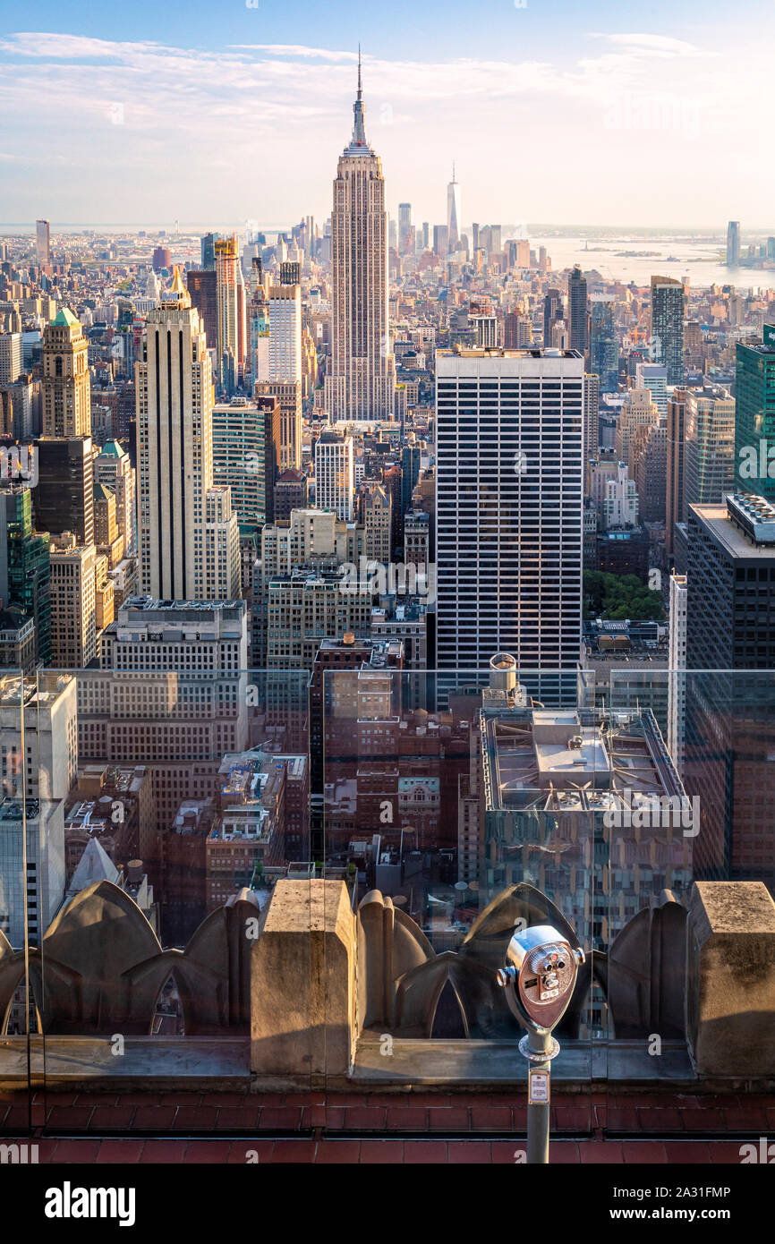 e of the iconic telescopes on Top of the Rock Observatory with the Empire State Building in the distance, New York City, USA. Stock Photo