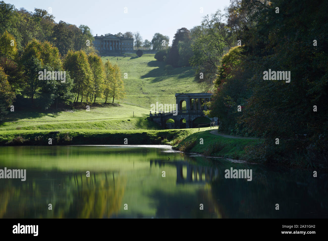 Prior Park Landscape Garden. View of the Palladian Bridge and the house from the lower lake. Bath. UK. Stock Photo