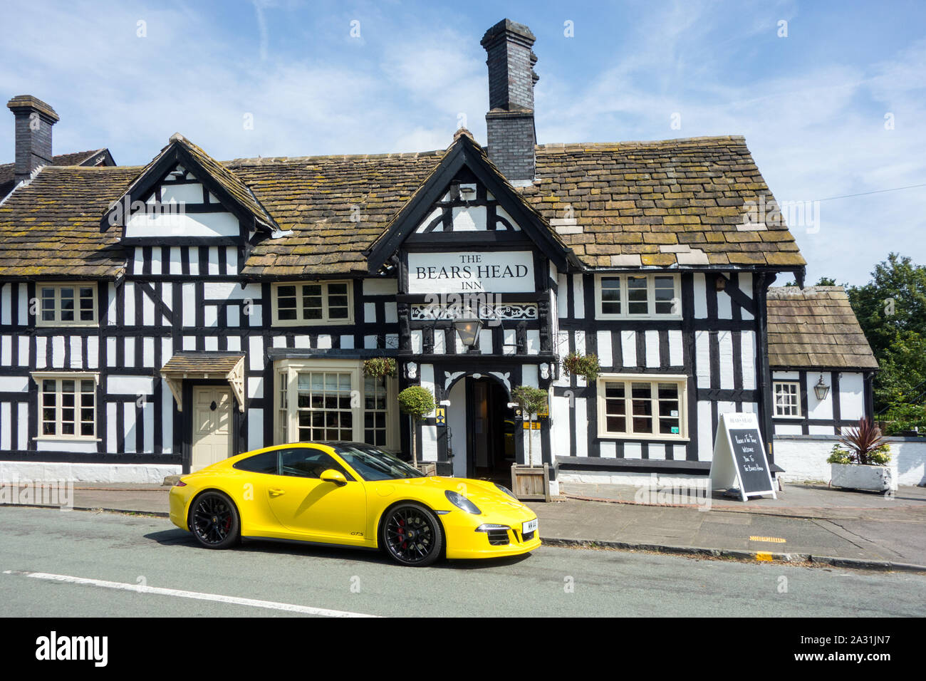 Yellow Porsche sports car parked outside a traditional English black and white half timbered inn public house at Brereton Cheshire England Stock Photo