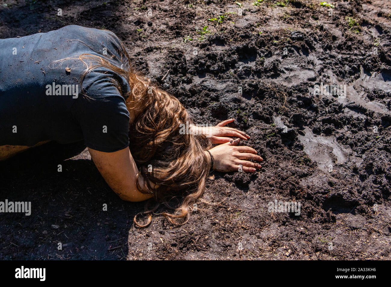 A closeup view of a young brunette woman, crouched over face down in a muddy puddle, seeking contemplation and enlightenment in nature during shamanic retreat. Stock Photo
