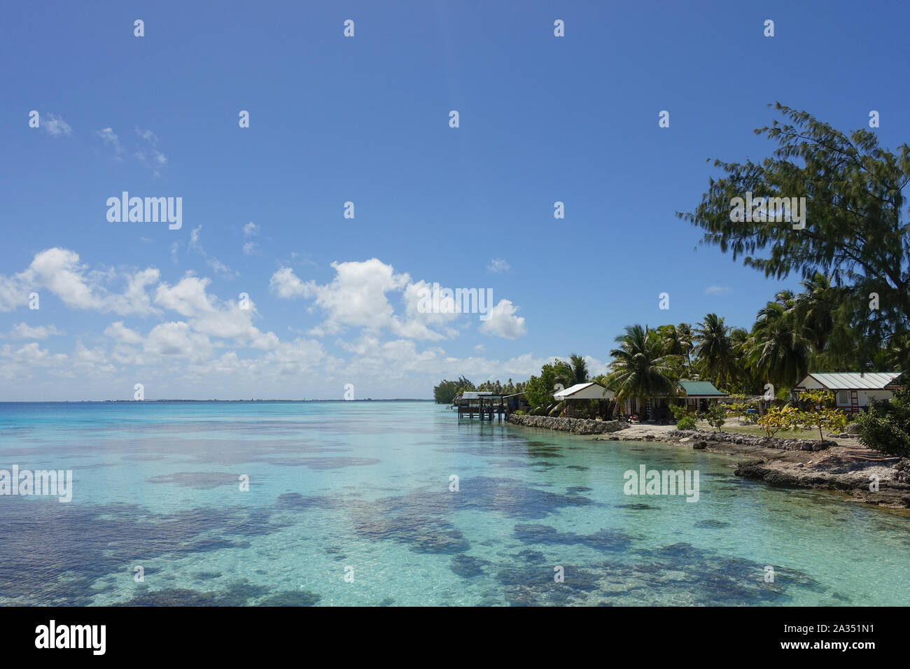 Houses and palm trees line the coast of a tropical lagoon on the island of Fakarava in French Polynesia Stock Photo
