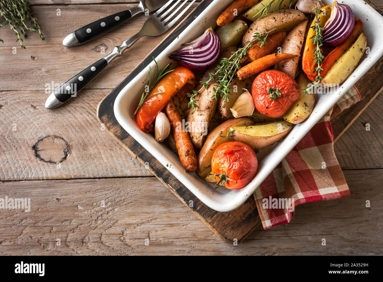 Oven roasted vegetables with spices and herbs in baking dish on wooden table. Vegetarian vegan  healthy organic autumn meal - baked vegetables. Stock Photo