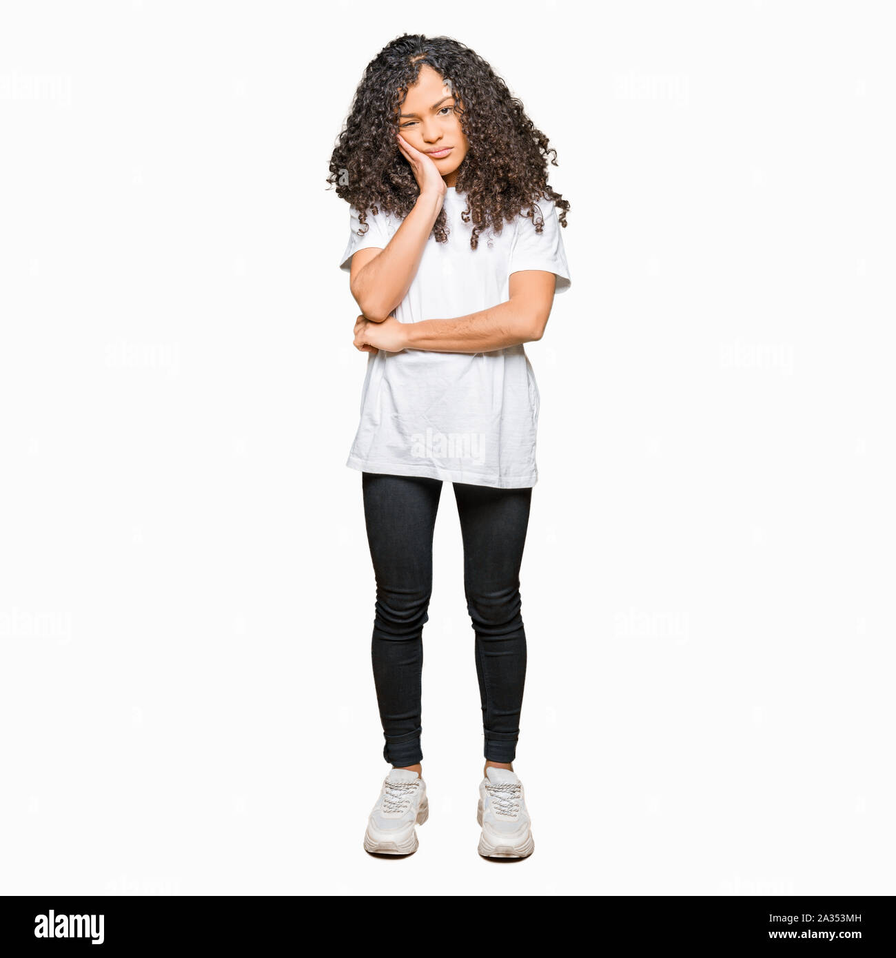 Young beautiful woman with curly hair wearing white t-shirt thinking looking tired and bored with depression problems with crossed arms. Stock Photo