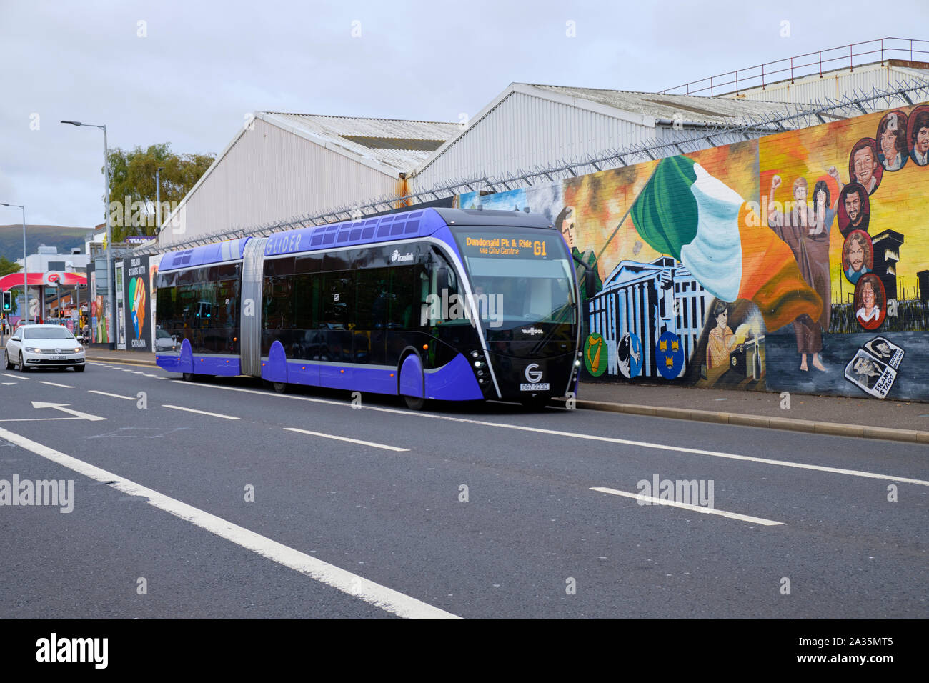 Glider transit,  Van Hool ExquiCity 18 vehicle in Belfast.  Bus on street of West Belfast passing by the International Wall of Peace Stock Photo
