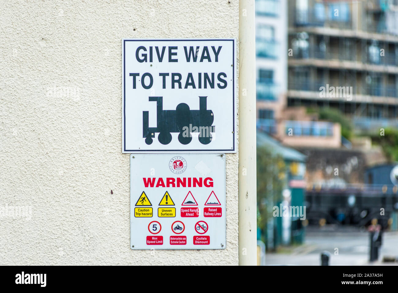 Give Way to Trains sign on Wapping Railway Wharf on Floating Harbour in Bristol, England, UK. Stock Photo