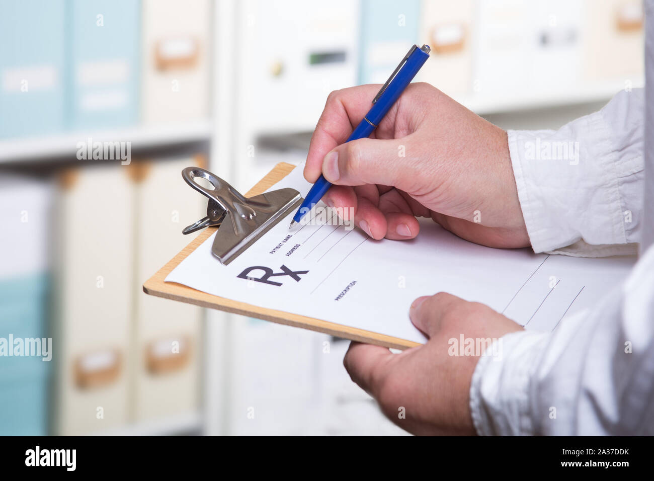 Male doctor filling patient complaints list clipped to pad. Physical, exam, disease prevention, ward round, prescribe remedy, healthy lifestyle concep Stock Photo