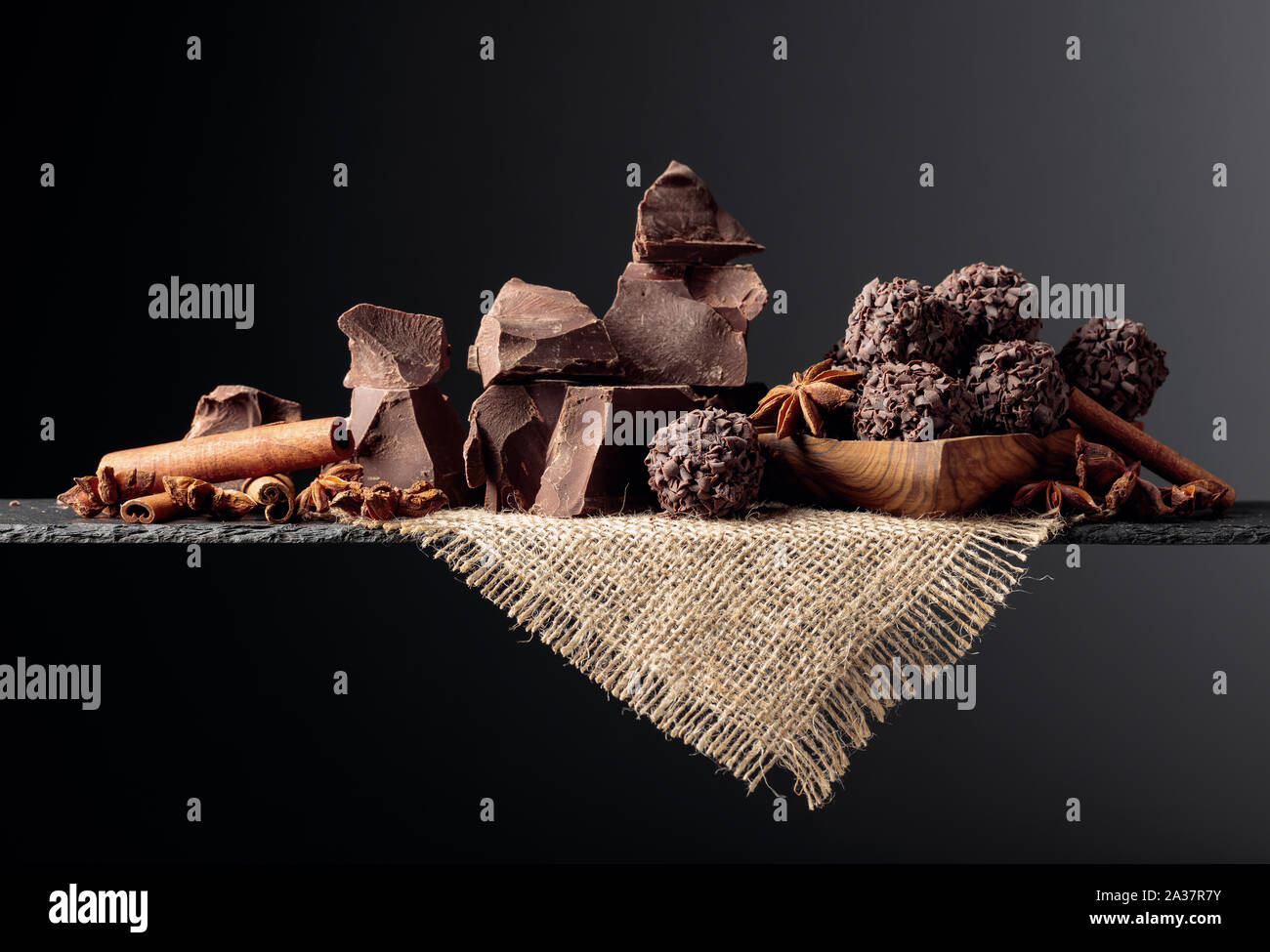 Chocolate truffles with broken pieces of chocolate and spices. Chocolate, cinnamon sticks and anise on a dark background. Copy space. Stock Photo