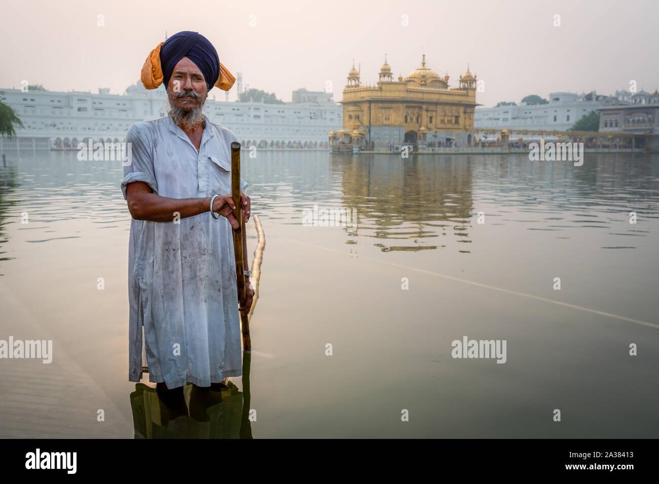 A Sikh cleans the Sarovar (water tank) – around the Golden Temple (Sri Harmandir Sahib),  Amritsar, Punjab, India Stock Photo