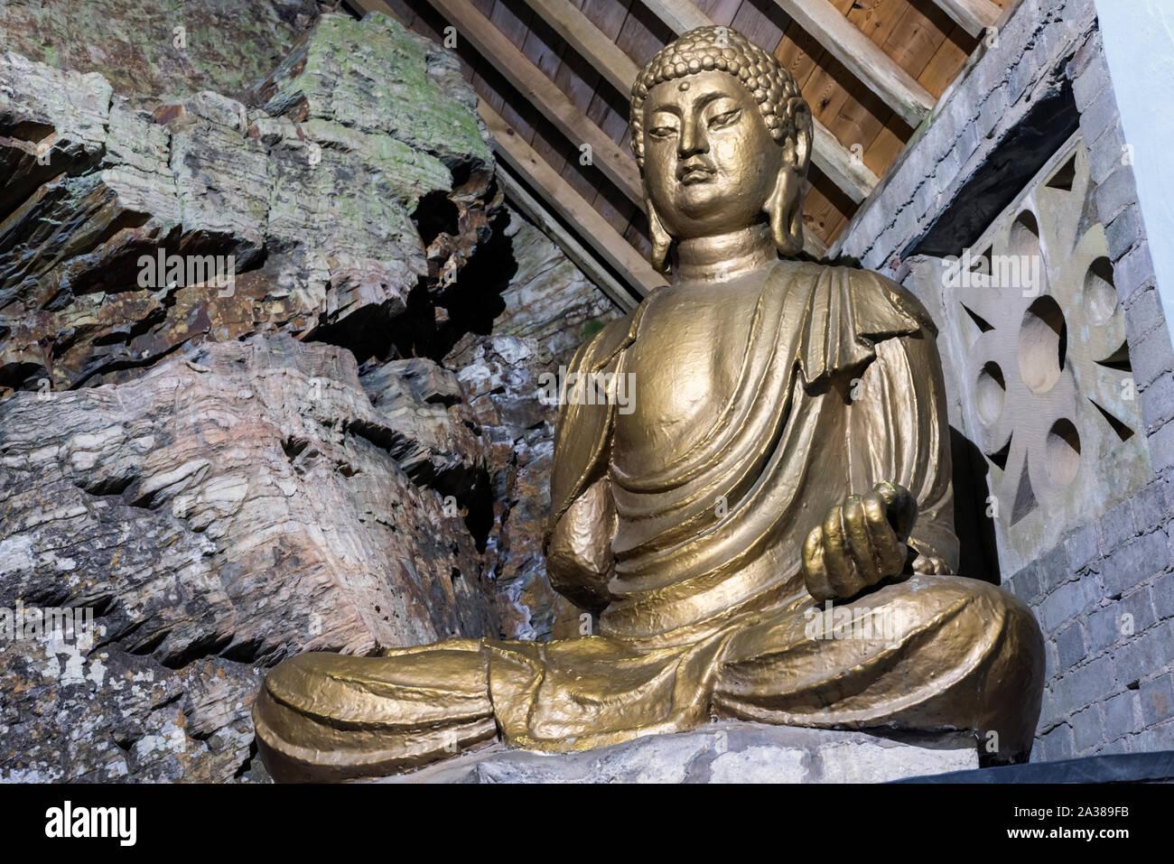 Golden Buddha statue at Portmeirion Village Stock Photo