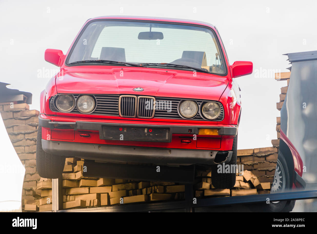 A red BMW car hangs precariously off the roof of a building, as if it had just broken through as the result of an accident, Rotterdam, Netherlands. Stock Photo