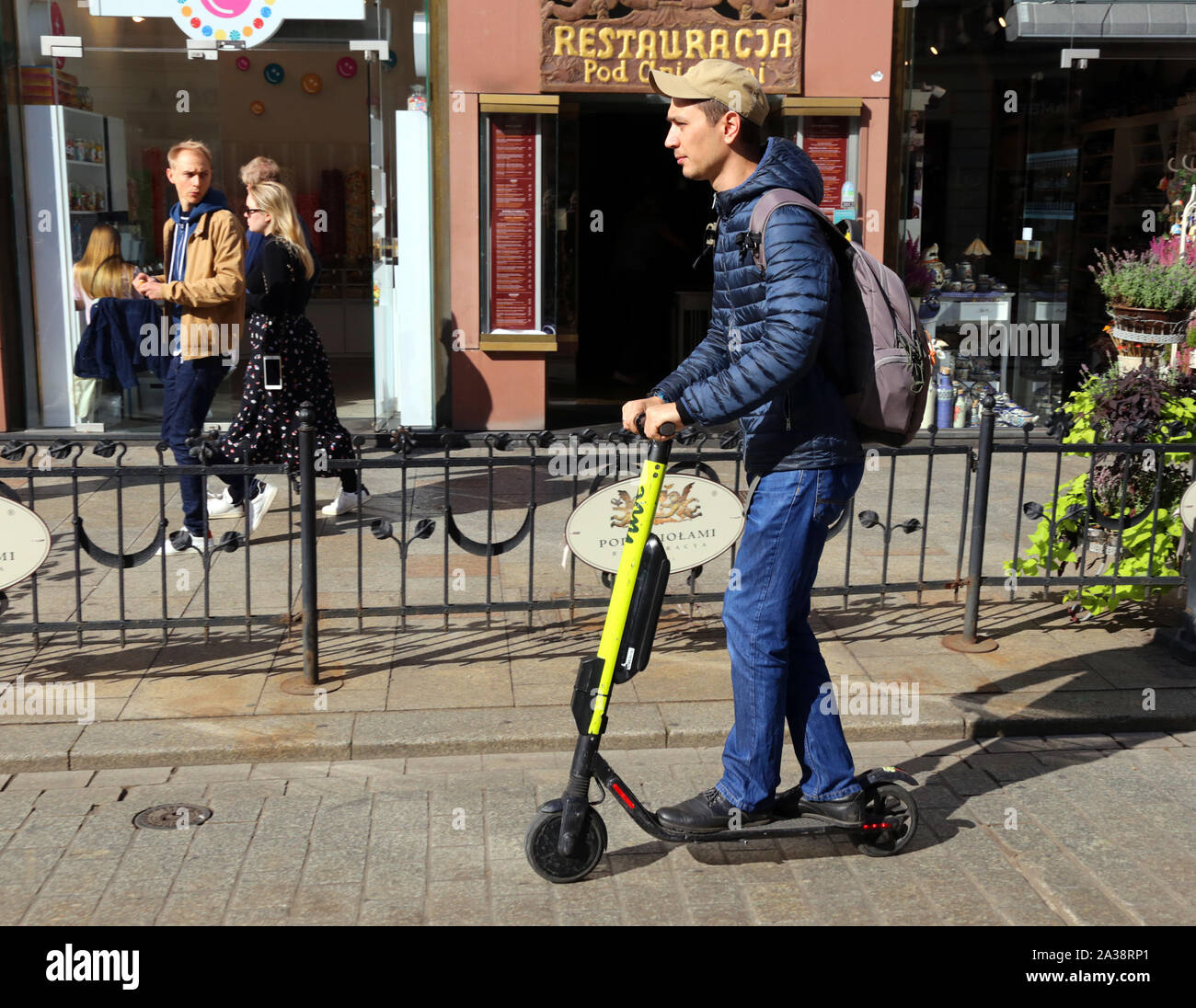 Cracow. Krakow. Poland. Young man riding electrik scooter on Grodzka Str. center of the Old Town. Stock Photo