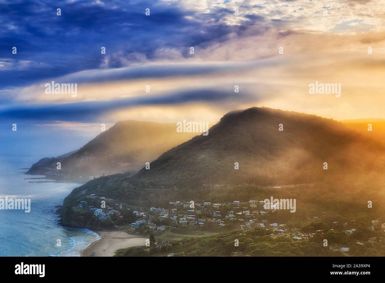 Range of gum-tree covered hills on South Coast off Sydney part of Grand Pacific Driver scenic route with famous Sea Cliff Bridge at sunset from elevat Stock Photo