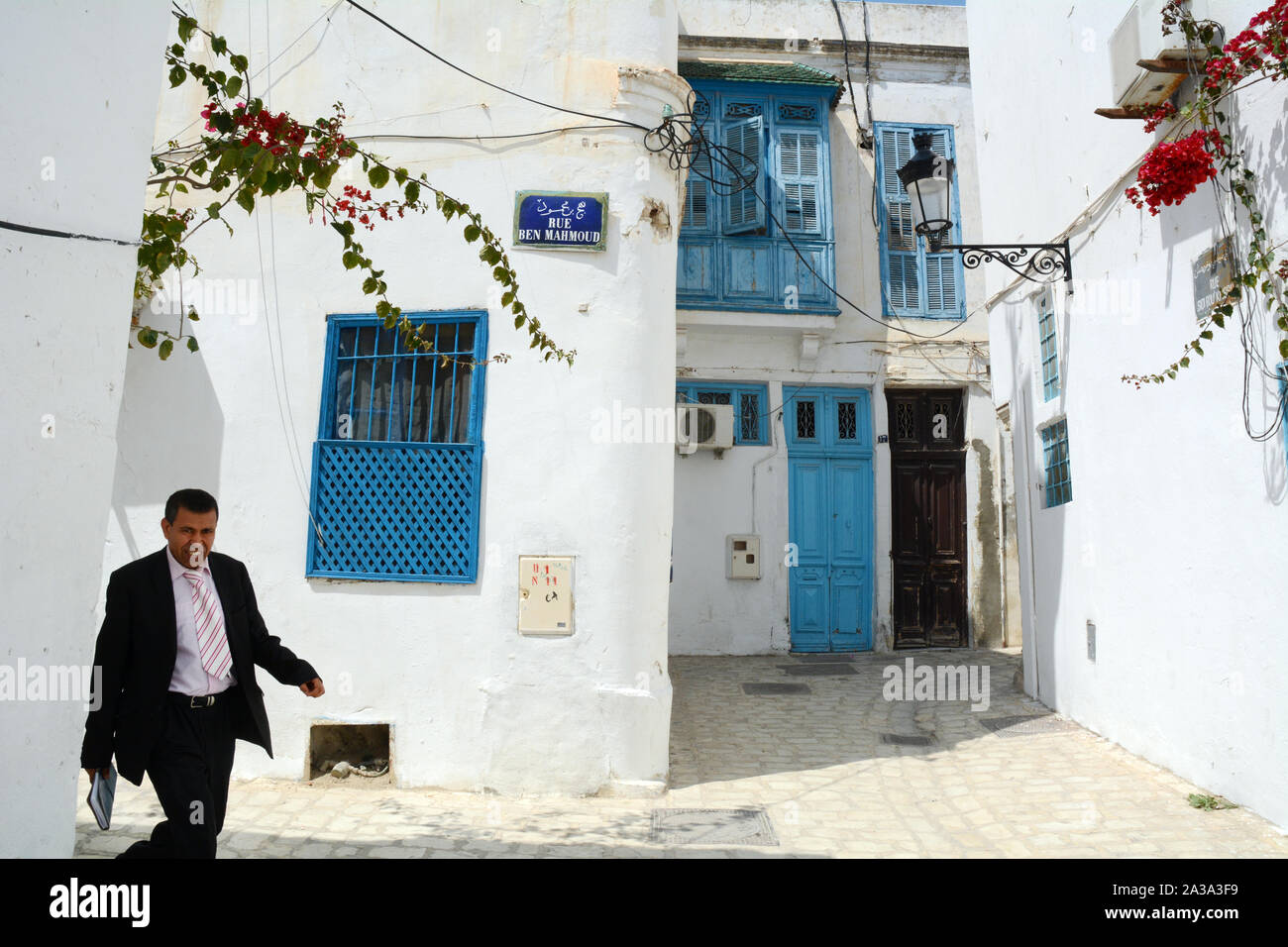 A middle-aged Tunisian man in a business suit walking through the pedestrian streets of the Hafsia quarter of the medina (old city) of Tunis, Tunisia. Stock Photo