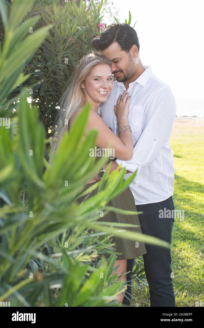 Man's head touching woman's head looking down. Woman facing camera. In-love and happy mixed race couple. Blonde woman and Turkish (Middle Eastern) man Stock Photo
