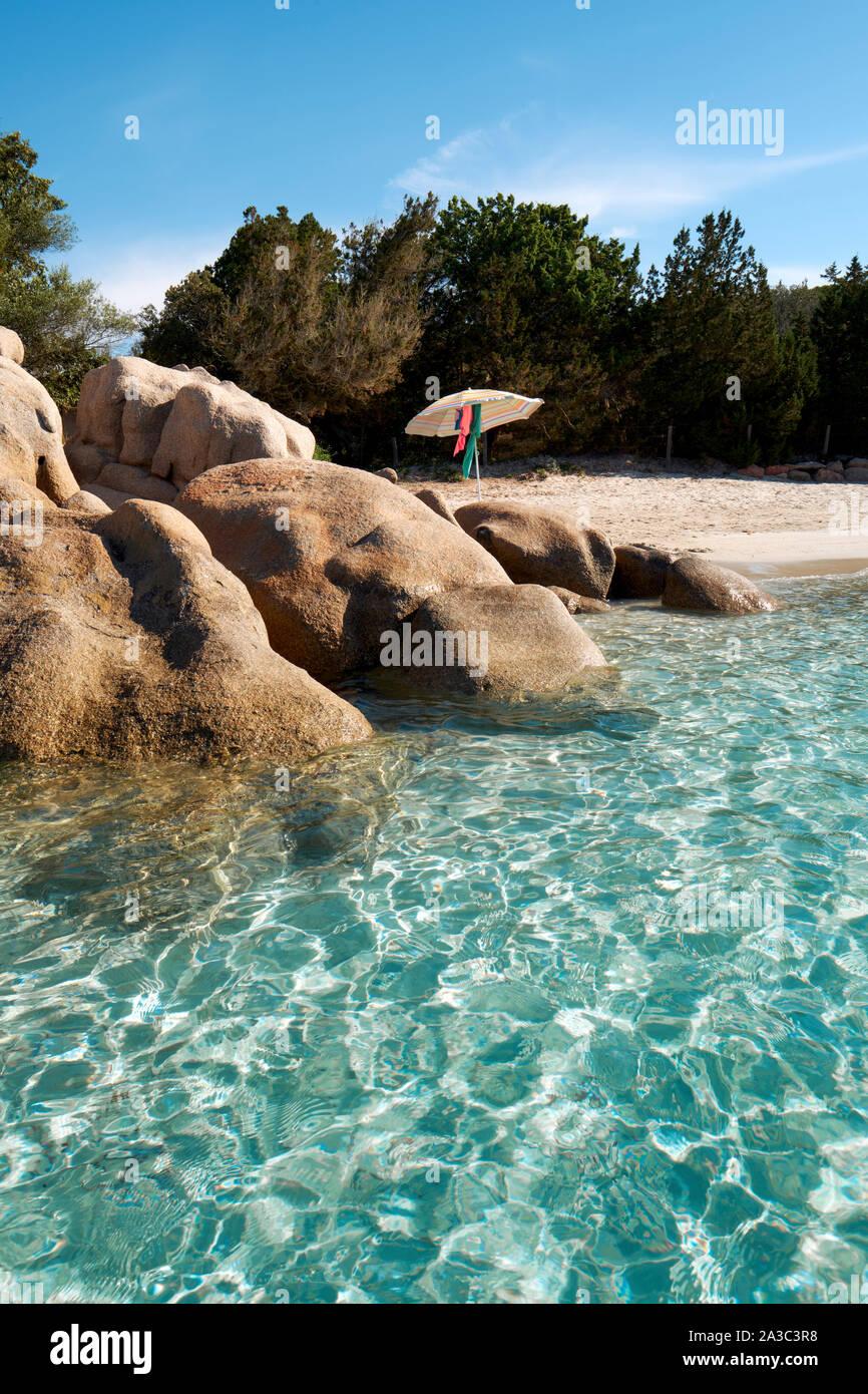A secluded clear water, white sand beach and rocks with parasol / Plage de Santa Giulia / Santa Giulia beach, Porto-Vecchio Corsica - Corsica beach Stock Photo