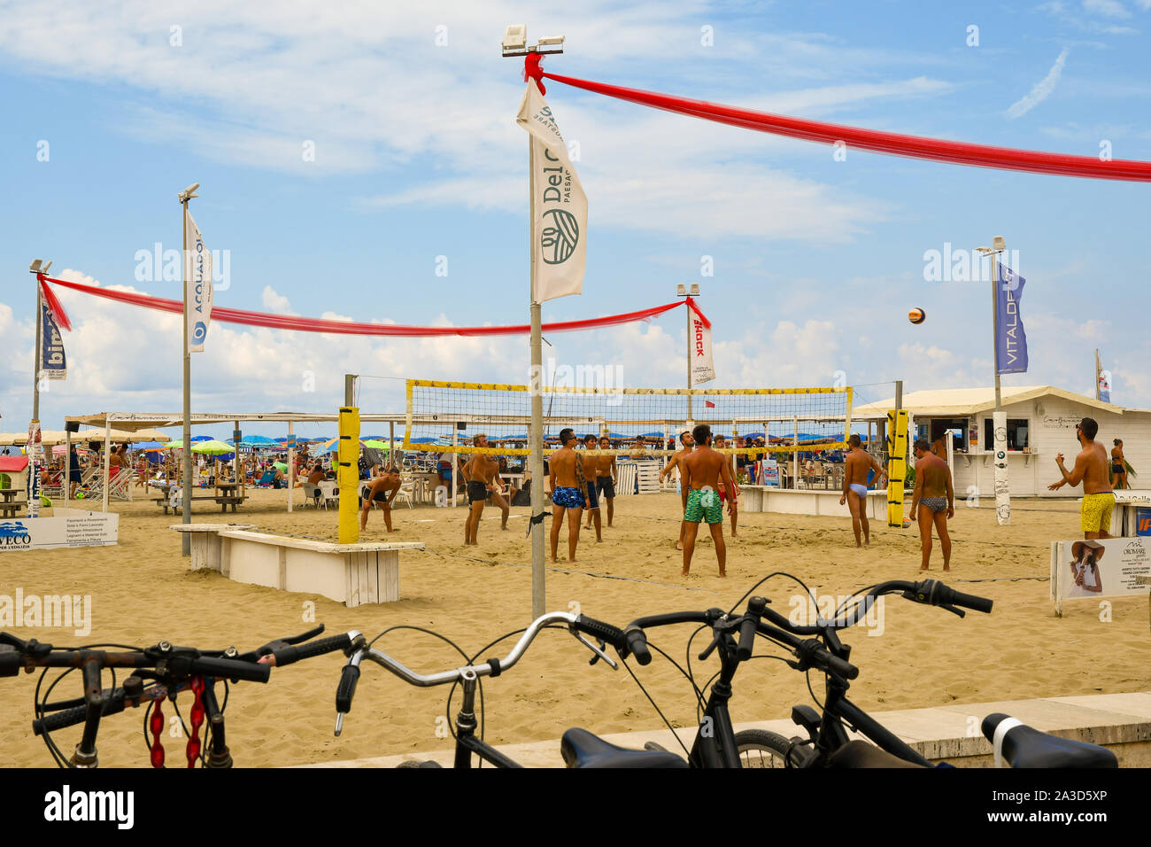 Young men playing beach volleyball on the sandy beach of Lido di Camaiore in a sunny mid-August day with parked bicycles, Versilia, Tuscany, Italy Stock Photo