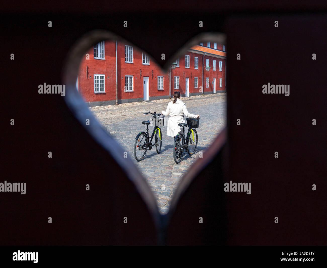 Frau oder Freundin schiebt 2 ausgeliehene Fahrräder durch eine skandinavische Stadt Stock Photo
