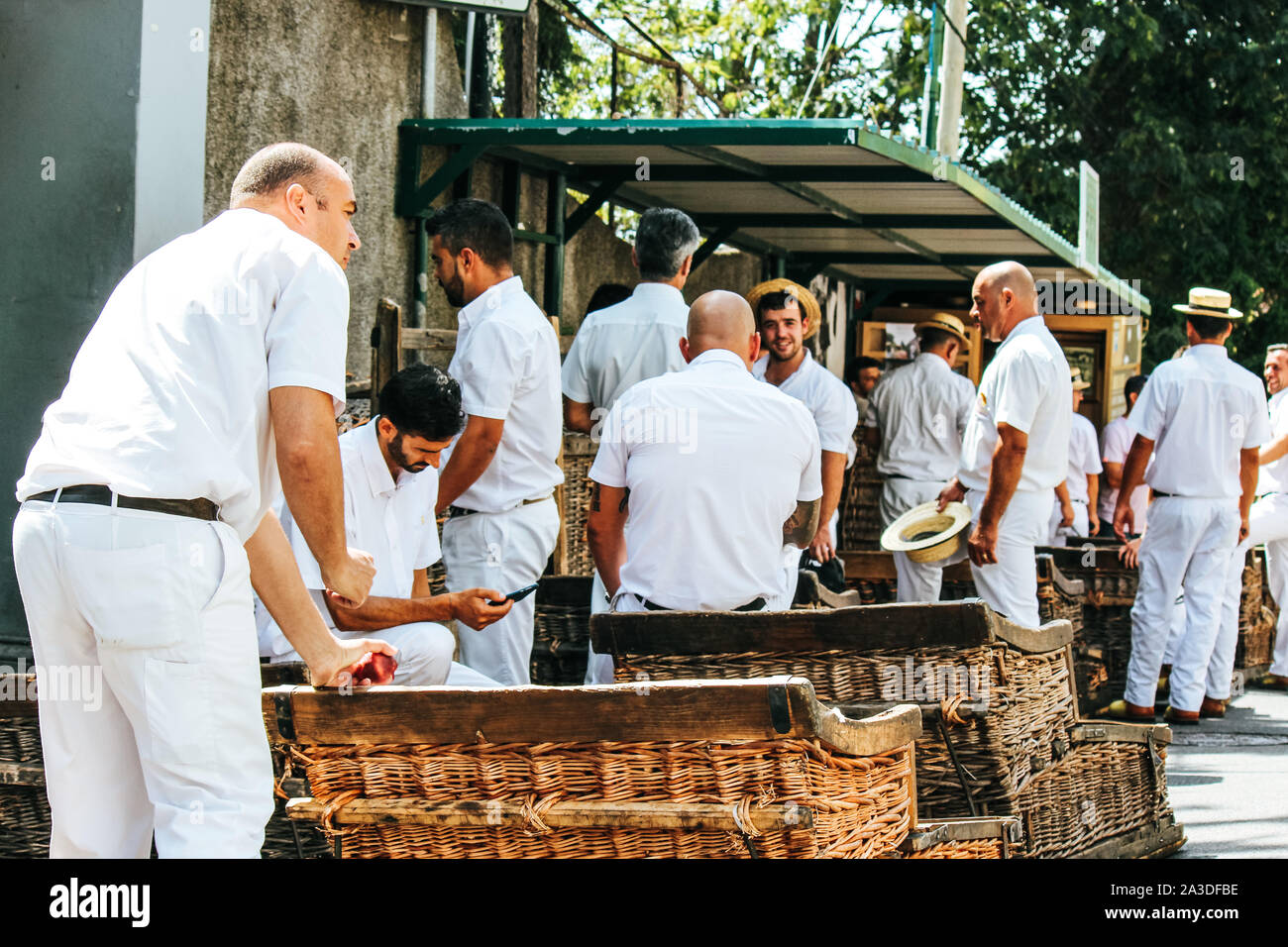 Monte, Madeira, Portugal - Sep 14, 2019: Wicker Basket Sledges drivers, Carreiros do Monte. Traditional mean of transport to Funchal, now a tourist attraction. Typical straw hats, white clothes. Stock Photo