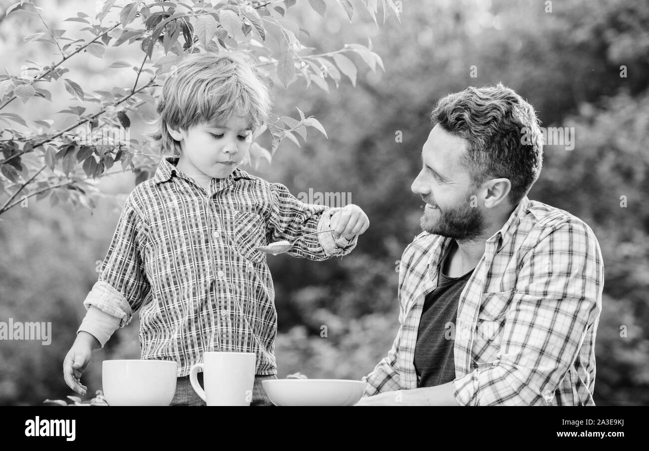 Little boy and dad eat. Organic nutrition. Healthy nutrition concept. Nutrition habits. Family enjoy homemade meal. Personal example. Nutrition kids and adults. Father teach son eat natural food. Stock Photo