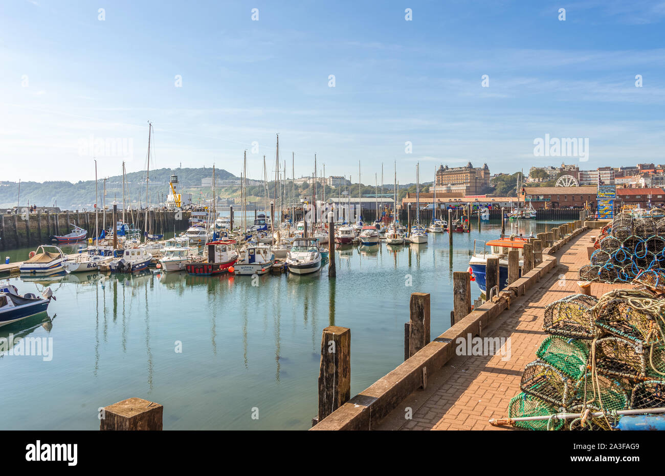 A marina lies beside a pier with a lighthouse and a wharf with a trawler is opposite. Lobster pots are in the foreground and a hill with hotels is in Stock Photo
