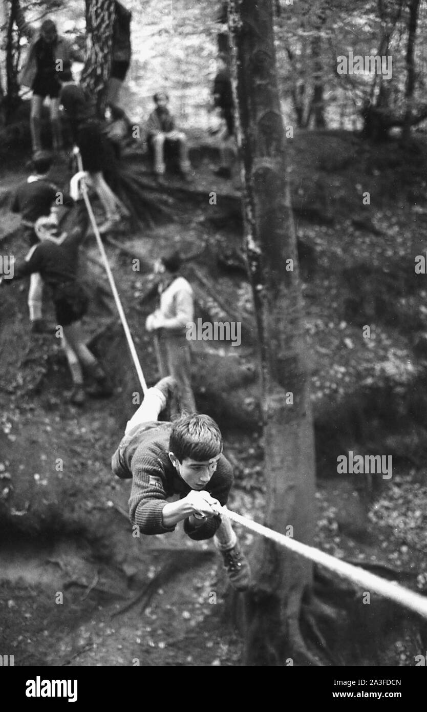 1960s, historical, a scout using his hands and feet lying on a rope to manoeuvre himself over a crossing out in wooded forest, England, UK. Stock Photo