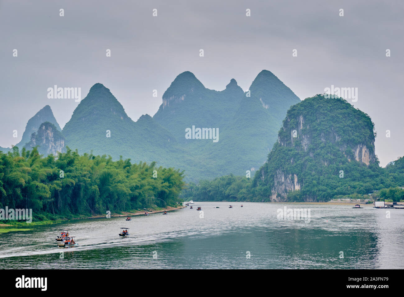 Tourist boats on Li river with carst mountains in the background Stock Photo