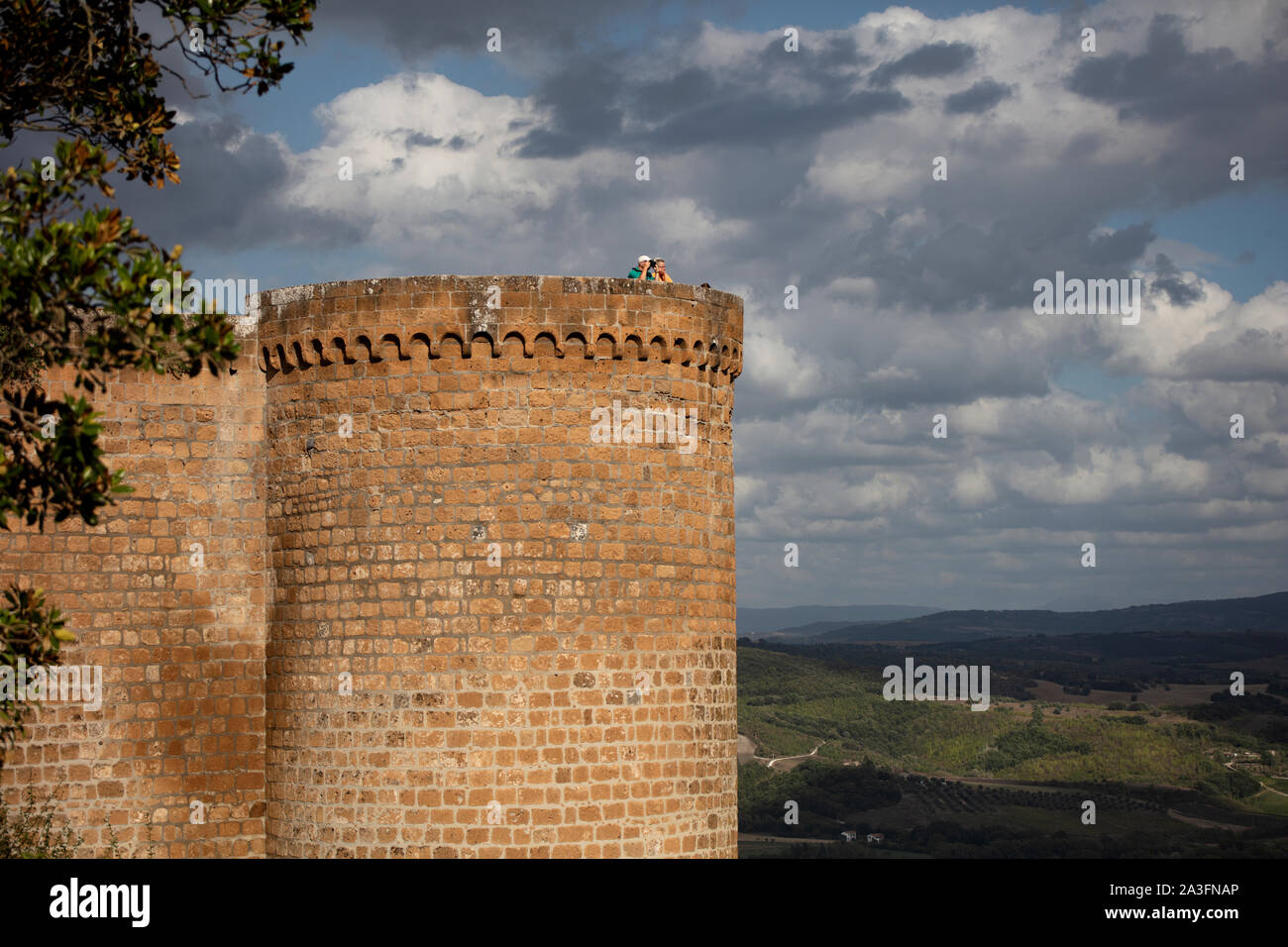 Tourists taking a picture from the top of a tower in the Fortezza Albornoz in Orvieto on a cloudy summer evening. Stock Photo