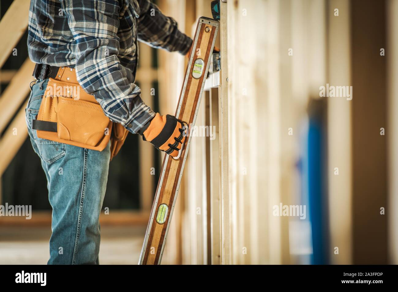 Contractor Worker Taking Spirit Level Tool to Make Sure the Wooden Frame Alignment is Correct. Construction Tools and Building Technologies. Stock Photo